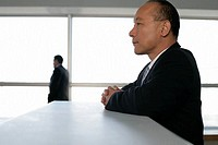 Asian Businessman resting upon a counter with a businessman in the background