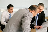 Three businessmen looking at a folder with documents