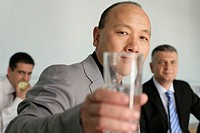 Asian businessman holding a glass at camera, two persons sitting in background