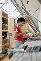 Grandfather and boy choosing CDs, fully-released