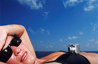 Woman wearing sunglasses, sunbathing with camera on chest, close-up