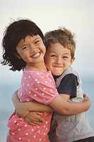 Girl and boy (7-9) embracing, outdoors, smiling, portrait