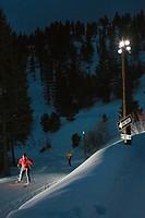 Woman nordic skiing at night.