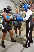 Women boxers sparring with coach