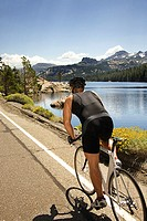 Man riding bicycle past Lake Tahoe, California , United States