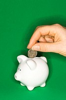 Inserting coin in piggy bank