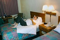 Adult male works on a laptop computer in a hotel room