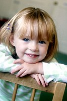 Headshot of a 3 year old girl smiling into camera at nursery