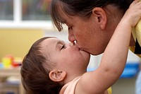 2 year old girl kissing one of the staff at nursery