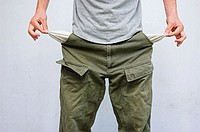 Young man pulling his pockets out to illustrate lack of money.