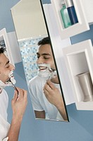 Man shaving in mirror.