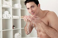 Man splashing water on face