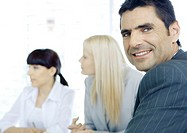 Businessman in meeting, smiling at camera (thumbnail)