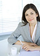 Businesswoman sitting at table with pen and cup of coffee, smiling at camera