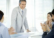 Business team applauding businessman