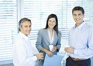 Three business colleagues standing in office with cups in hands, smiling at camera
