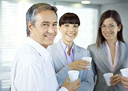 Business colleagues standing in office with cups in hands, smiling at camera
