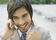 Businessman using cell phone, smiling, and clenching fist
