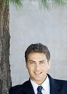 Businessman next to tree, portrait