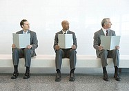 Three men in suits sitting in a row, holding up files, and looking away