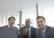 Three businessmen with laptop, smiling and pointing at camera
