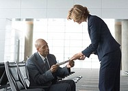 Airline attendant handing seated businessman a ticket
