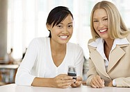 Two female office workers, holding cell phone, smiling
