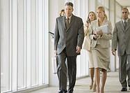 Executives walking through corridor of office building