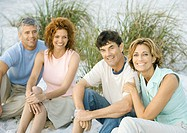 Two mature couples sitting on beach