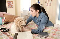 Teenager in bedroom with dog
