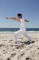 Man doing yoga on beach.