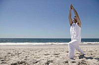 Man doing yoga on beach.