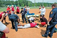 Player with broken leg is attended to by fire personal and wife as team members look on while laying on ball field during softball game