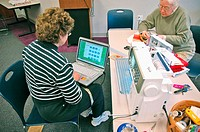 Women working in Quilting Class with needles and computers to make quilts as gifts and wall hangings from fabrics and cloth to patterns