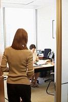 Rear view of a businesswoman standing at the door with another businesswoman in the background