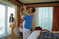 Side profile of a young couple with their son and daughter in a hotel room