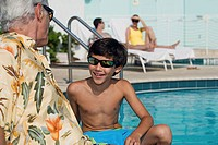 Side profile of a senior man sitting with his grandson at poolside