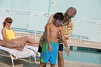 Senior man holding his grandson from behind at poolside