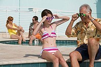 Senior man sitting with his granddaughter at poolside wearing swimming goggles