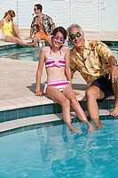 Senior man sitting with his granddaughter at poolside and smiling