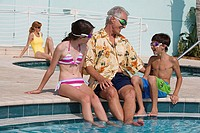 Senior man sitting with his grandson and granddaughter at poolside
