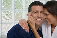 Close-up of a mid adult woman embracing a mid adult man and smiling