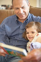 Close-up of a girl sitting with her grandfather and reading a book