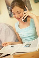 Close-up of a teenage girl talking on a cordless phone while reading a magazine