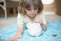 Close-up of a girl inserting a coin into a piggy bank
