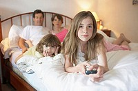 Close-up of a teenage girl and her sister with their parents lying in the bed watching TV