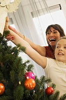 Close-up of a grandmother and her granddaughter decorating a Christmas tree
