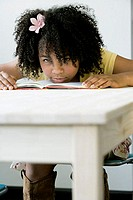 Portrait of a girl leaning on a book on a table