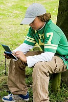 Side profile of a boy using a personal data assistant in a park
