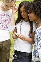 Close-up of two girls listening to music with another girl standing beside them